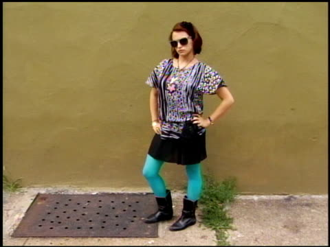 Young Woman wearing patterned top and black skirt with boots black hair bow sunglasses and teal tights