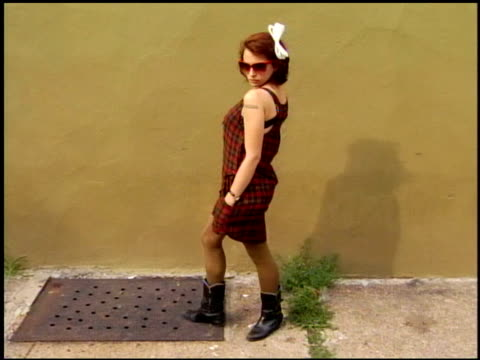 young woman wearing plaid top and skirt with boots white hair bow sunglasses and tan tights - hair accessory stock videos and b-roll footage