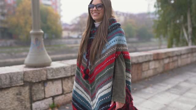 vídeos y material grabado en eventos de stock de mujer joven usando poncho caminando en la ciudad el día de otoño - distante
