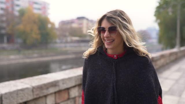vídeos y material grabado en eventos de stock de joven mujer usando poncho caminando en la ciudad en el hermoso día de otoño - vestimenta para mujer