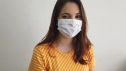 Young woman wearing pretective face mask looking at camera.