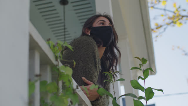 young woman wearing protective face mask leans on porch railing of house - railings stock videos & royalty-free footage