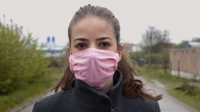 stockvideo's en b-roll-footage met jonge vrouw die beschermend gezichtsmasker draagt - breed