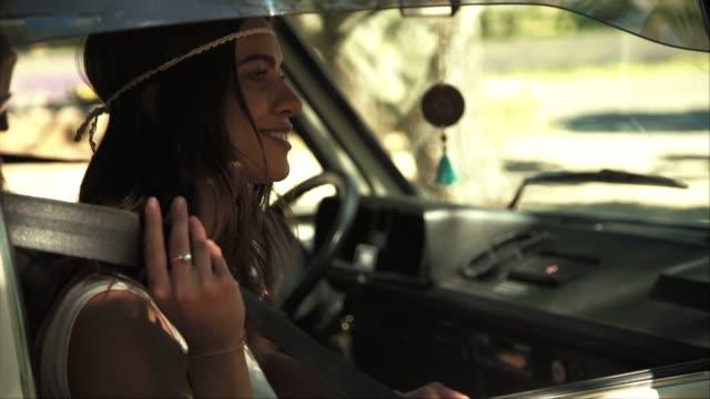 vídeos de stock e filmes b-roll de young woman wearing seat belt in van - viagem em estrada