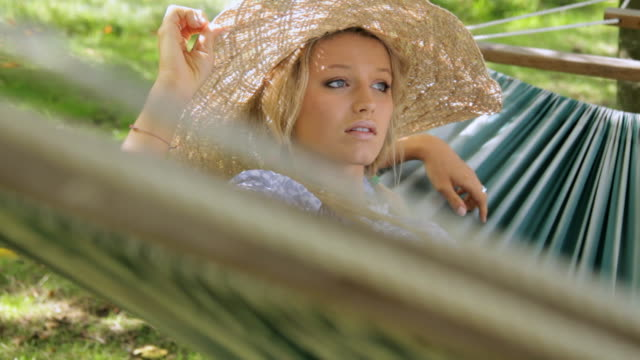 cu young woman wearing straw hat relaxing in hammock / london, united kingdom - straw hat stock videos & royalty-free footage