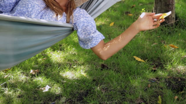 cu tu young woman wearing straw hat relaxing in hammock / london, united kingdom - one young woman only stock videos & royalty-free footage
