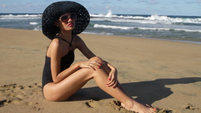 Young woman wearing sunglasses and sunhat sitting on beach