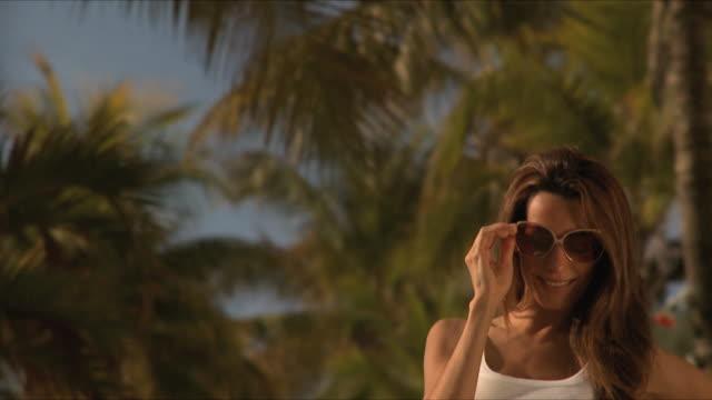 SLO MO CU Young woman wearing sunglasses laughing / South Beach, Florida, USA