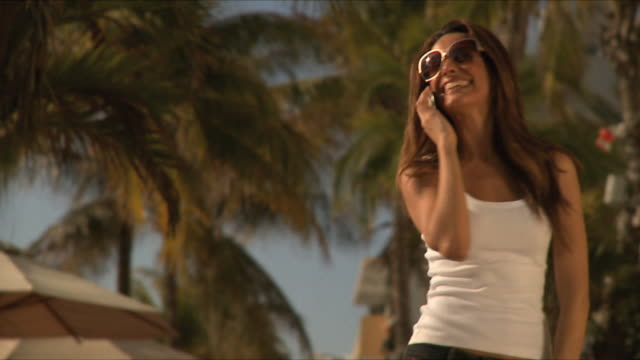 SLO MO MS Young woman wearing sunglasses talking on mobile phone, laughing / South Beach, Florida, USA