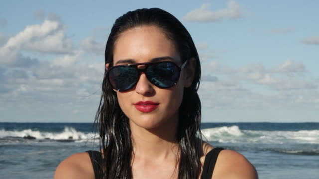 Young woman wearing sunglasses turning to camera