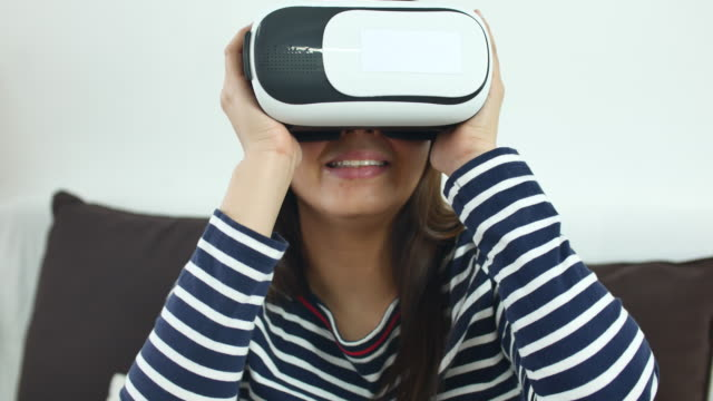 Young woman wearing virtual reality headset at home