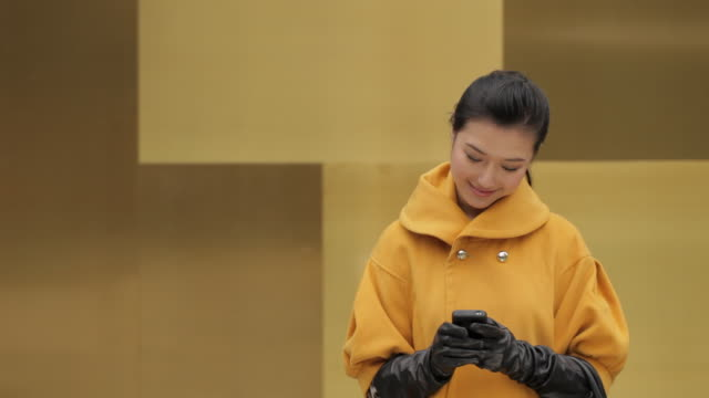 ms young woman wearing yellow coat using mobile phone and smiling - formal glove stock videos and b-roll footage