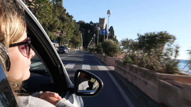 young woman wears headphones while riding in passenger seat - passenger seat stock videos & royalty-free footage