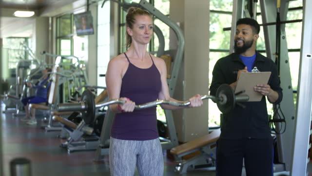 young woman weightlifting with a coach in a gym - 自己改善点の映像素材/bロール