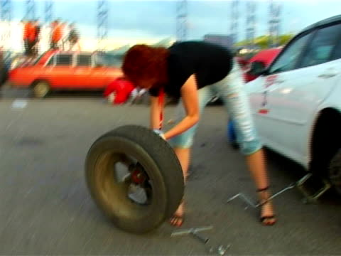 young woman wheel change in car. unscrewing - wheel stock videos and b-roll footage