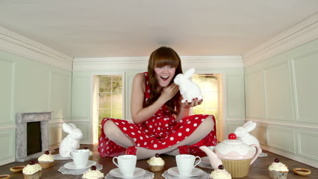 young woman whispering with rabbit figure in small room - tea party stock videos and b-roll footage