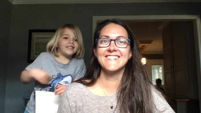 a young woman who is working from home introduces her daughter to a video conference call. - teamwork stock videos & royalty-free footage