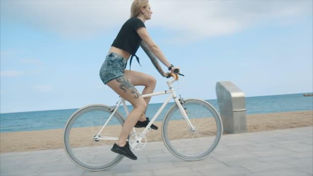 junge frau mit fahrrad - shorts stock-videos und b-roll-filmmaterial