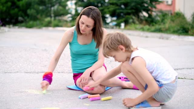 と若い女性お子様は、チョークでアスファルト - チョーク点の映像素材/bロール