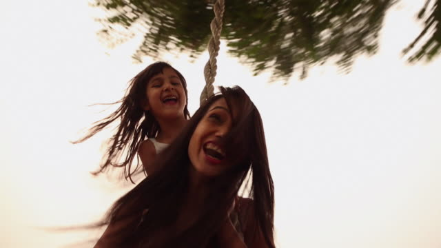 vidéos et rushes de young woman with a girl enjoying rope swing, haryana, india - balançoire