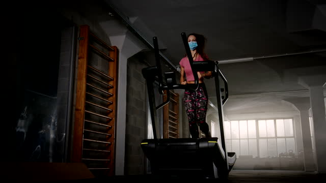 slo mo young woman with a mask running on treadmill at the dusty health club - treadmill stock videos & royalty-free footage
