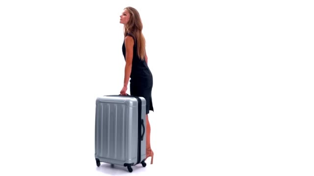 Young woman with a suitcase waiting and looking around