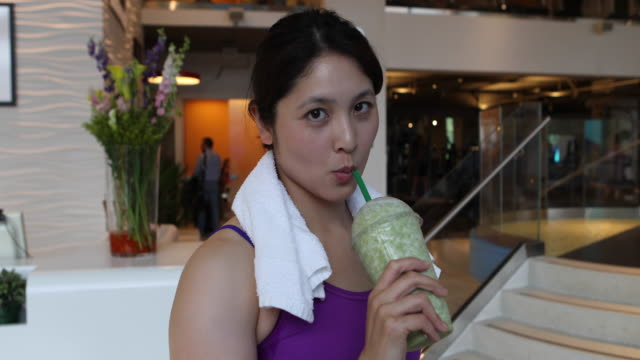 Young woman with a towel around her neck, drinking a smoothie beverage after a workout.