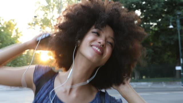 vidéos et rushes de jeune femme avec la danse afro de modèle de cheveux dans la rue - la vingtaine