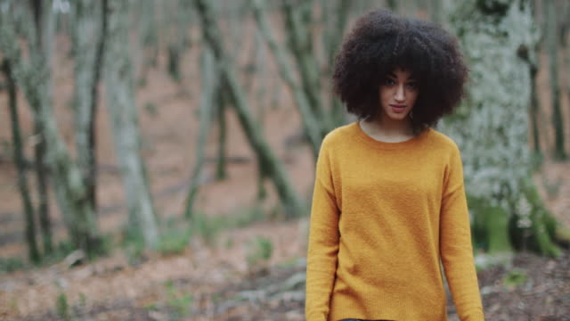 vídeos de stock e filmes b-roll de young woman with afro hairstyle exploring the woods - afro
