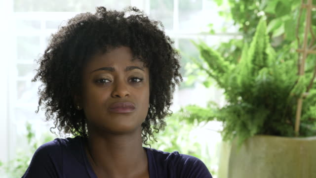 Young woman with afro rolling eyes and looking displeased.