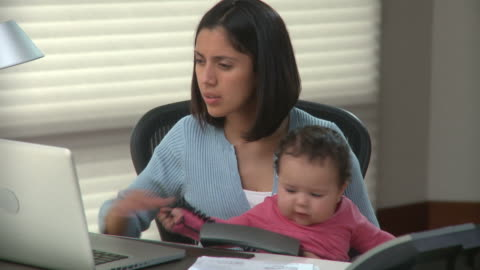 ms tu young woman with baby girl (6-11months) on laps paying bills on line in home office / richmond, virginia, usa - multitasking stock videos & royalty-free footage