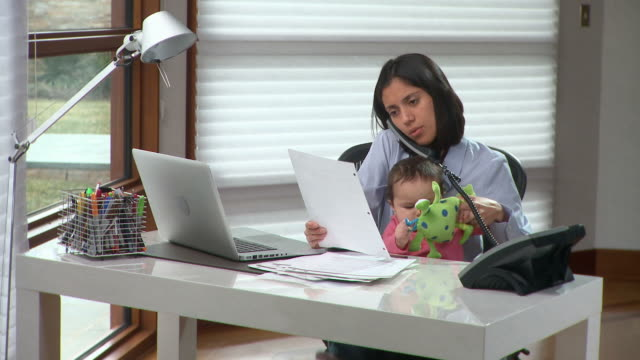 MS Young woman with baby girl (6-11months) on laps talking on phone and using laptop in home office / Richmond, Virginia, USA