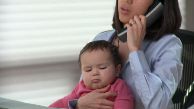 ms tu td young woman with baby girl (6-11months) on laps talking on phone in home office / richmond, virginia, usa - 6 11 months stock-videos und b-roll-filmmaterial