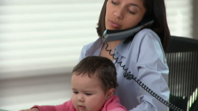 cu pan, young woman with baby girl (6-11months) on laps talking on phone in home office / richmond, virginia, usa - berufstätige mutter stock-videos und b-roll-filmmaterial