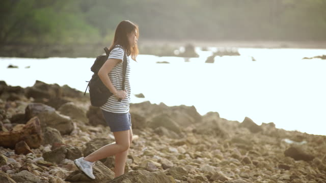 Young woman with backpack enjoying view on beach.