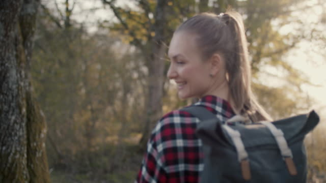 vídeos de stock e filmes b-roll de young woman with backpack walking in forest - outono