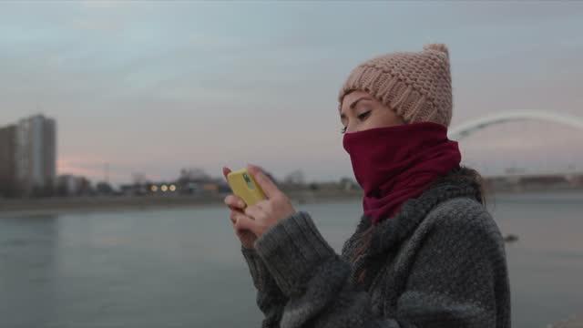 giovane donna con bandana che cammina sul lungomare e scatta foto del paesaggio urbano con il telefono - cappotto invernale video stock e b–roll