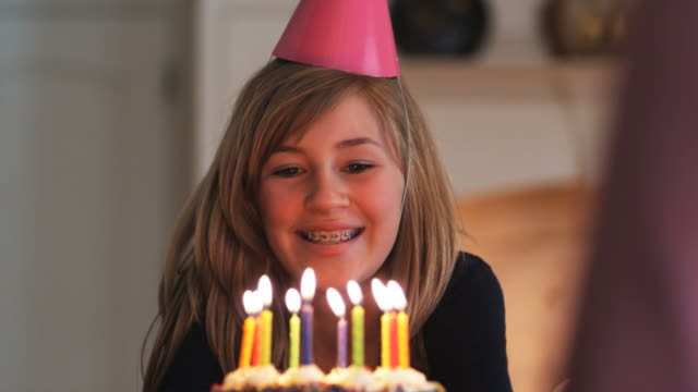 vídeos de stock e filmes b-roll de young woman with braces blowing out the candles on a birthday cake - 12 13 anos