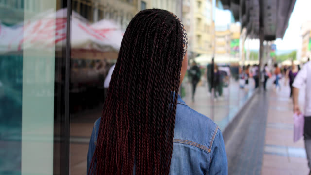 young woman with braided hair walking through city streets and smiling - rear view stock videos & royalty-free footage
