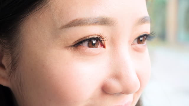 cu young woman with brown eyes - 瞬き点の映像素材/bロール