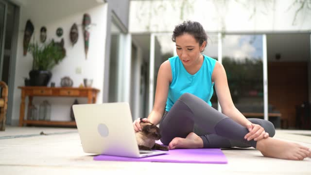 young woman with cat at home doing virtual exercise class - generation z stock videos & royalty-free footage