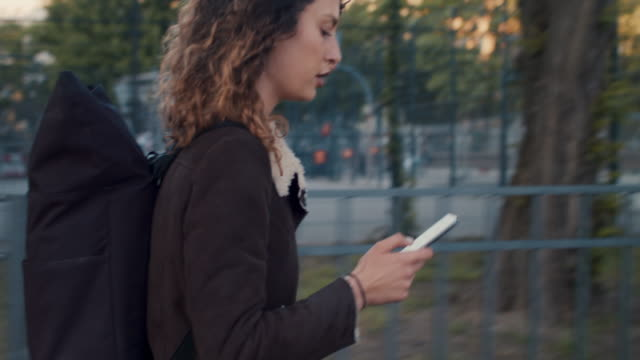 young woman with cell phone walking in berlin - leben in der stadt stock-videos und b-roll-filmmaterial
