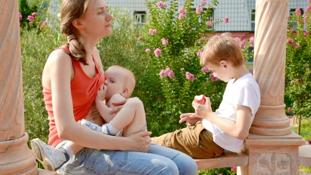 young woman with children in summer gazebo - breastfeeding stock videos & royalty-free footage