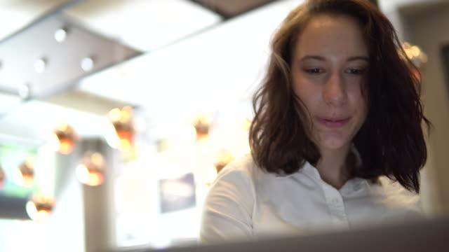 junge frau mit kreditkarte und bezahlen rechnungen online im kaffee-shop laptop - only young women stock-videos und b-roll-filmmaterial
