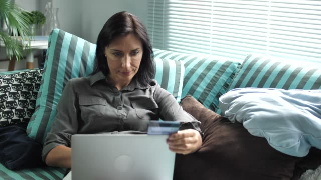 Young woman with credit card and laptop paying bills online