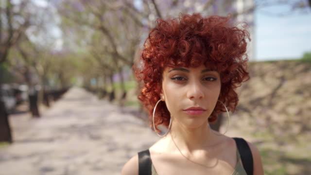 vídeos de stock, filmes e b-roll de mulher nova com cabelo vermelho encaracolado que está no parque - cabelo ruivo