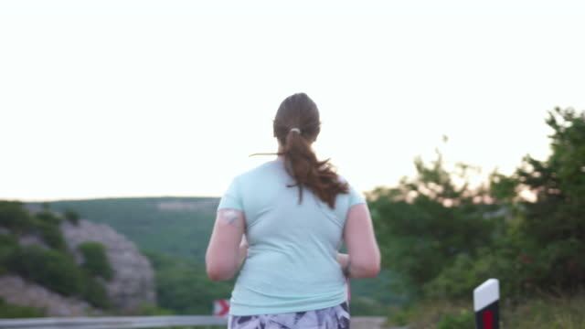 young woman with diabetes wearing a cgm and running in nature - diabetes stock videos & royalty-free footage