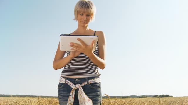 stockvideo's en b-roll-footage met hd crane: young woman with digital tablet in field - volkoren