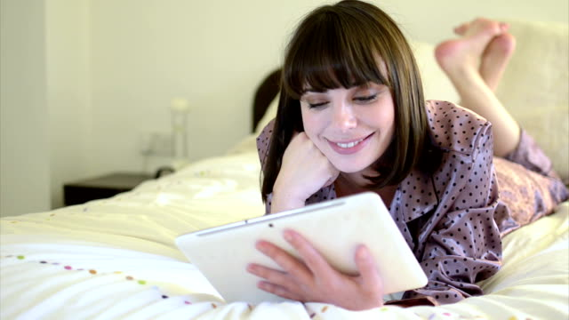 vídeos de stock, filmes e b-roll de jovem mulher com tablet digital em movimento - reclinando