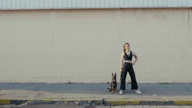 vidéos et rushes de young woman with dog in front of a wall - plan large